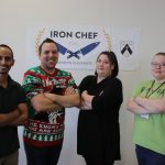 Four people stand with crossed arms in front of an Iron Chef Brandon University poster