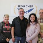 Four people stand in front of an Iron Chef Brandon University poster