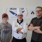Three people stand in front of an Iron Chef Brandon University poster