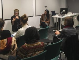 Two women sit in front of an audience. The woman on the left is gesturing as she speaks