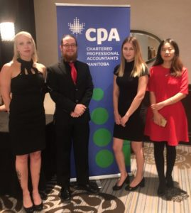 "Two pair of people stand. In between is a standup banner that says ""CPA"" in large letters"