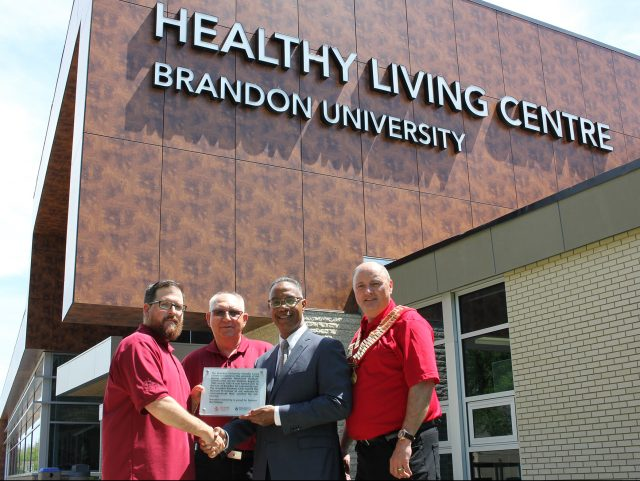 Representatives of Kinsmen Club of Brandon and Brandon University pose outside of Healthy Living Centre.