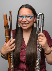 A woman smiles while holding various types of flutes