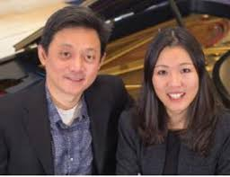 Ning Lu and Jie Lu pose, smiling, in front of a piano