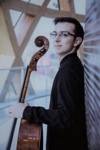 A man leans against a wall and looks to his side while holding a cello