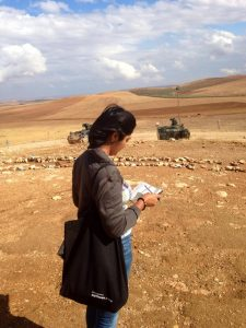 A woman is seen from the back writing in a notebook in the desert. Armoured vehicles are in the distance.