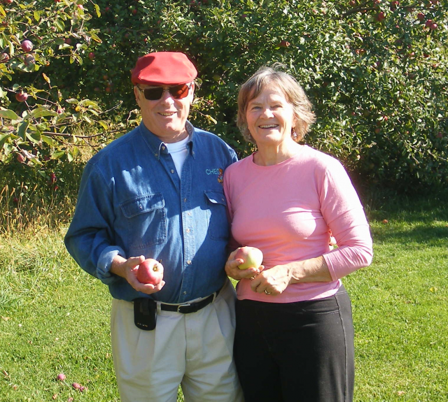 A man and woman stand in a treed area. Each of them is holding an apple.
