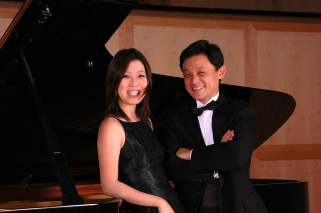 Ning Lu leans on a grand piano and Jie-deng Lu stands next to her with his arms crossed.