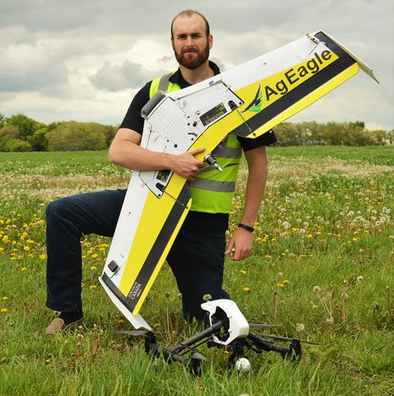 Matthew Johnson kneels on one knee in an open field, holding a winged drone in front of his body with his left arm, while another drone is on the ground in front of him