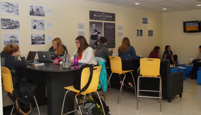 Several students sit at tables and in lounge furniture studying in the McCutcheon Alcove. A plaque and historical pictures can be seen on the wall.