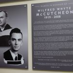 Two photos of Wilfred McCutcheon are on the left, next to the dedication plaque.