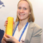 A woman smiles while holding up a gold brick