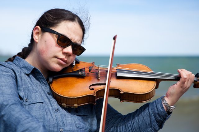 A person wearing sunglasses plays a viola with a body of water behind them