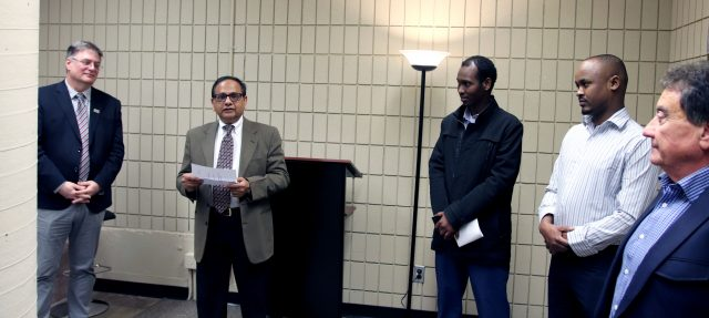 A man holds a piece of paper while speaking. Another man stands on the left of the picture, while three other men stand on the right side of the photo.