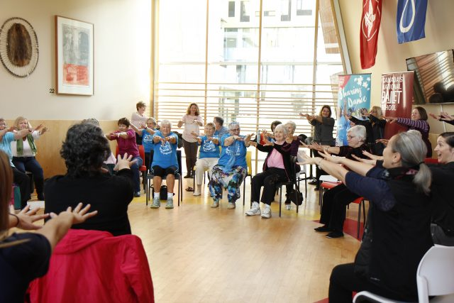 A large number of seniors sit in chairs in a large circle with their arms straight out in front of them.