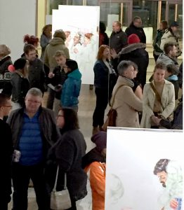 A crowed of people stand in the art gallery, with images on display in the foreground and in the back of the photo