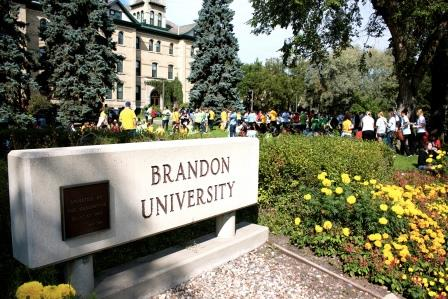 Photo of Brandon University sign, with Clark Hall in the background