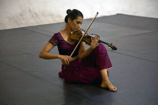 Dr. Parmela Attariwala plays the violin as she sets with her legs crossed on a black floor in a room with white walls.
