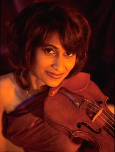 Close shot of Parmela Attariwala's face as she poses with her violin under her chin in the playing position.