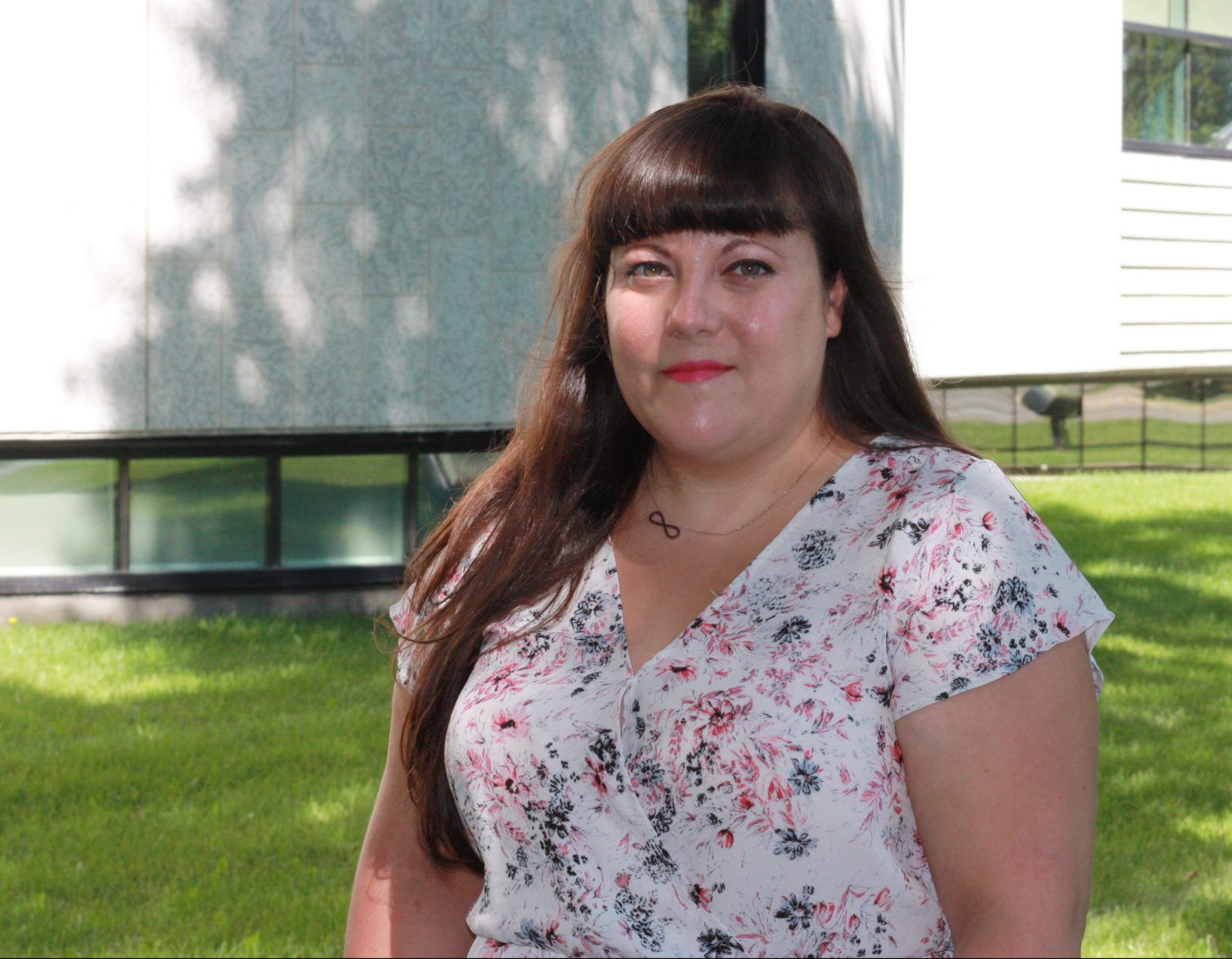 Penny Tryphonopoulos poses in front of the Dr. James & Lucille Brown Health Studies Complex at Brandon University