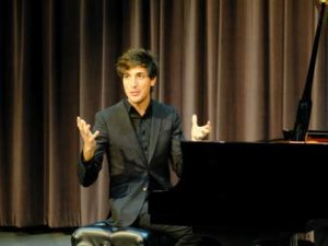 A man gestures with both hands while sitting at a piano