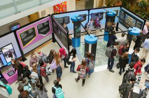 A large group of students mingle and look at exhibition displays