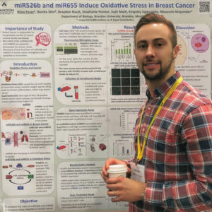 A man holds a coffee cup while standing next to a research poster