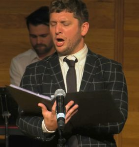 A singer performs into a microphone as he reads the music book in front of him. Another performer is seen in the background.