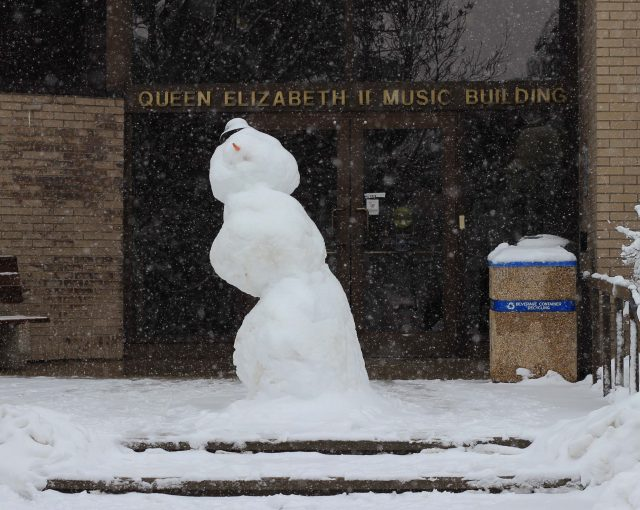 "A large snowman stands on a snowy day in front of the doors of the building. The sign above the door reads ""Queen Elizabeth II Music Building"""