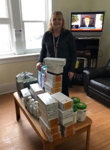 A woman stands behind a table wth several containers of medical supplies on top of it.