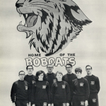 "Members of the swim team stand in two rows in front of a wall that features a large Bobcat logo and the text ""Home of the Bobcats."""