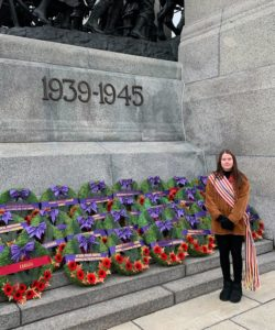 A woman stands in front of a World War II memorial and wreaths