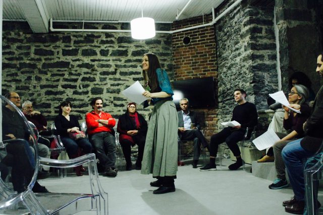 An actor reads from a script while surrounded by audience members and other actors.