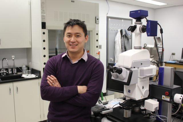 Chen crosses his arms and smiles for the camera while standing in his lab. To the right of Chen in the photo is a large microscope.