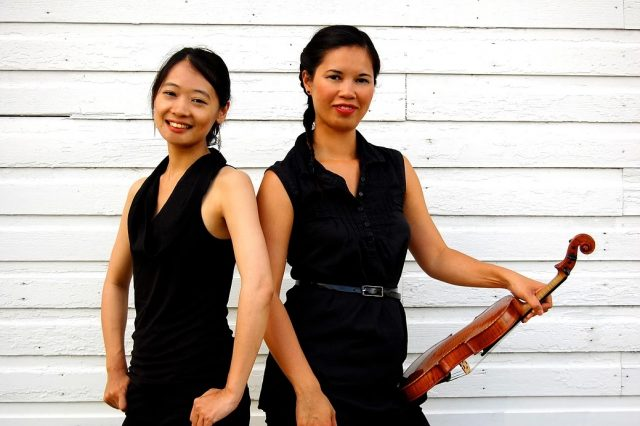 Niekawa and DuWors pose side-to-side, with the backs slightly turned toward one another in front of a white, wooden wall. DuWors holds a violin at her left hip.