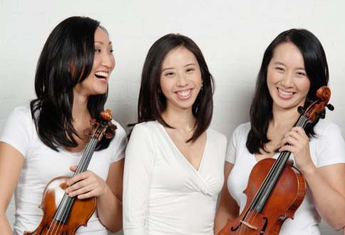 Three women pose in front of a white wall. The woman on the left is looking at the other two, who are looking at the camera. The women on each end are holding violins.