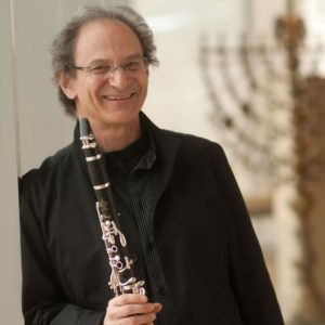 A man leans against the wall and smiles while holding a clarinet in one hand