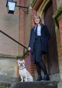 A woman stands in the doorway of a brick building with a dog sitting beside her