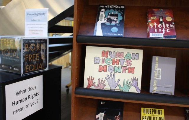 "A sign proclaiming Human Rights Month and a number of books can be seen on a bookshelf. Also pictured is a ballot box above a sign the reads ""What does Human Rights mean to you?""."
