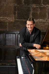 Murray McLachlan leans on a piano and smiles while standing in front of a stone and wooden wall.