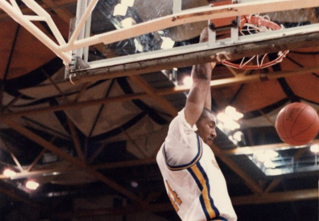 A man slam dunks a basketball in a vintage Brandon Bobcats photo.