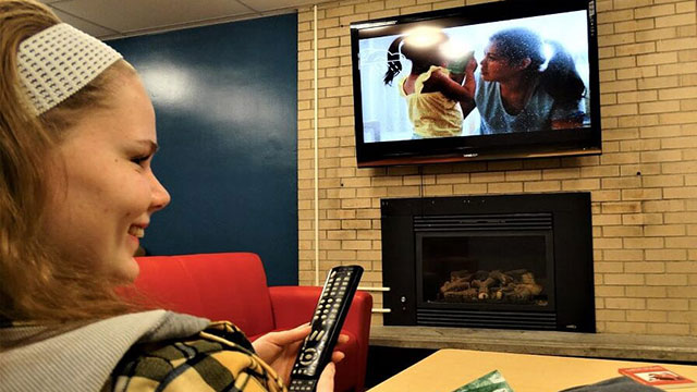 A student enjoying the comforts of the TV room in the basement of Flora Cowan Hall