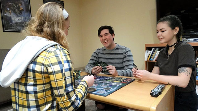 A gathering of students enjoying a board game.
