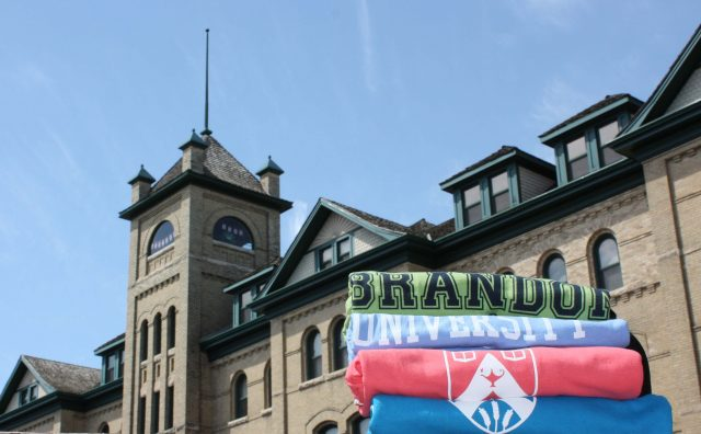 Green, purple, pink and blue t-shirts are seen in the foreground, with Clark Hall in the background